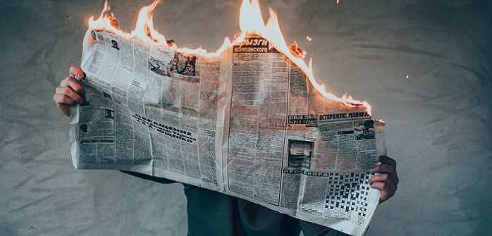 man holding newspaper on fire