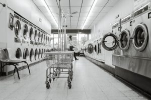 Grayscale photo showing metal laundromat carts at the center and machines on the side. A figure is in soft focus in the back carrying a basket.