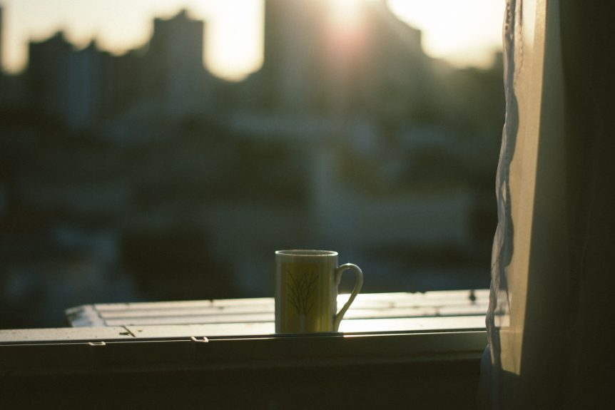 a mug sits in front of an open window with a curtain on the side and a city in blur in the background