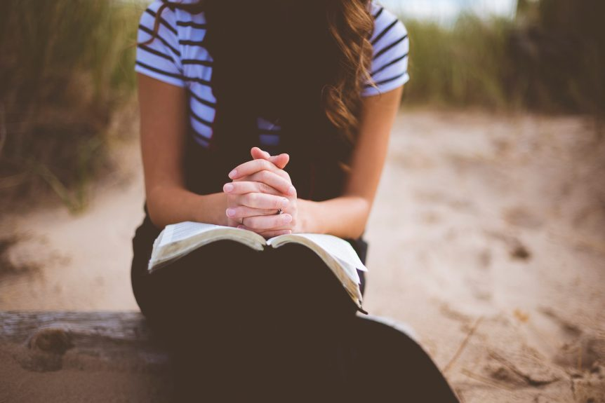 Soft focus image of a woman with praying hands resting on an open Bible. Behind her is a beach scene with sand and sea grass.