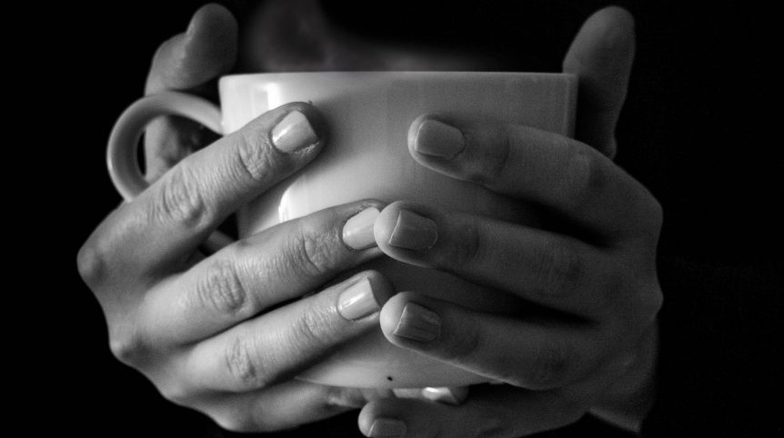 black and white image of hands holding a white mug