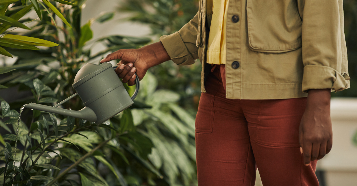 A woman watering a garden with a watering can.